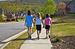 女孩三个走的年轻人 免版税库存照片