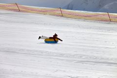 女孩下坡在滑雪胜地的雪管的 免版税图库摄影