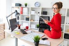 女孩下来坐桌在她的办公室并且拿着一支铅笔和文件在她的手上 图库摄影