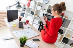 女孩下来坐桌在她的办公室并且拿着一支铅笔和文件在她的手上 免版税库存图片