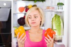 女孩不快乐的看起来红辣椒,冰箱 免版税库存图片