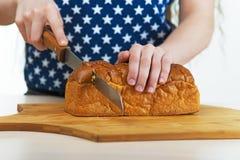 女孩与刀子的剪切面包 免版税图库摄影