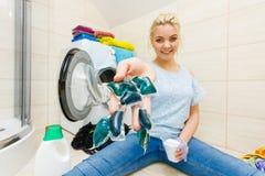 女孩与另外洗涤剂的洗涤洗衣店 免版税库存照片