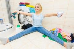 女孩与另外洗涤剂的洗涤洗衣店 免版税库存图片