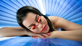 女孩与在日光浴室保护玻璃 免版税库存照片