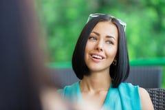 女孩与坐在小餐馆的朋友谈话 免版税库存图片