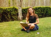 女孩与她的膝上型计算机一起使用在公园 免版税库存照片