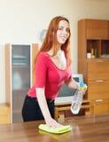 女孩与家具擦亮剂的清洁桌在客厅 库存照片