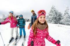 女孩与家庭的滑雪者滑雪在山 免版税图库摄影