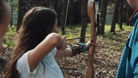 女孩与弓的射击箭头在有教练员的城市公园 股票录像