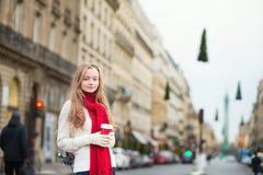 女孩与拿走在一条巴黎人街道上的咖啡 免版税库存照片
