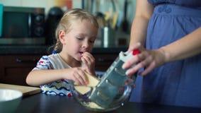 女孩与母亲的磨碎乳酪和吃它 股票视频