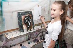 女孩与气刷的少年油漆在一个艺术性的演播室-俄罗斯,莫斯科- 2016年1月24日明亮地上色了图片 免版税库存照片