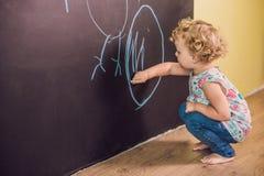 女孩与白垩的小孩油漆在黑板 免版税图库摄影