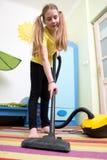 女孩与真空吸尘器的清洁地板 免版税库存照片