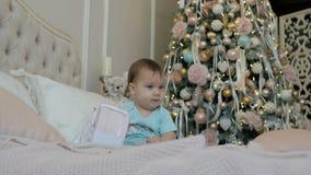 女孩与礼物在床坐圣诞树的背景 股票视频