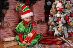 女孩与礼物的圣诞节矮子在Xmas冷杉木附近 免版税库存照片