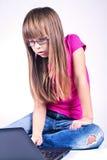 女孩与膝上型计算机一起使用 库存图片