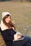 女孩与膝上型计算机坐长凳在公园 图库摄影