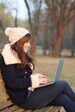 女孩与膝上型计算机坐长凳在公园 免版税库存照片