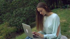 女孩与计算机一起使用在露天 影视素材