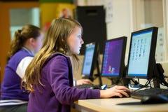 女孩与计算机一起使用 免版税库存照片