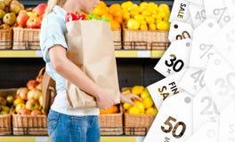 女孩与选择柠檬的新鲜蔬菜的手袋以一个好价格 免版税库存图片