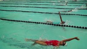 女孩严谨地在接踵而来的体育运动游泳竞赛的仰泳被训练 活动公共 股票视频