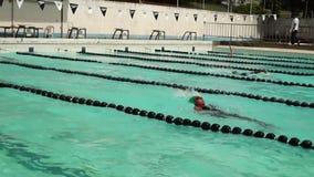 女孩严谨地在接踵而来的体育运动游泳竞赛的仰泳被训练 活动公共 影视素材