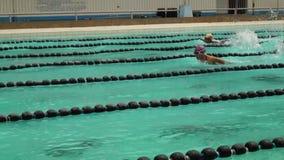 女孩严谨地在接踵而来的体育运动游泳竞赛的蝶泳被训练 活动公共 影视素材
