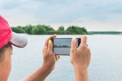 女孩为一台手机照相机的一个湖照相 免版税库存图片