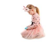 女孩为拿着鸡蛋的复活节穿戴了,隔绝 免版税库存照片