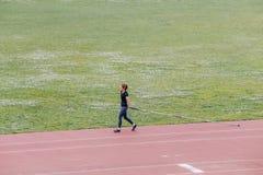 女孩为撑竿跳高做准备在体育场内 库存照片