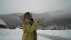 女孩为滑雪做准备 年轻女性滑雪者享用从天空下落的雪花 落对手的雪花 股票视频