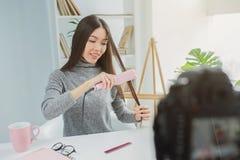 女孩为straitning她的头发使用特别设备 她记录那在她的秀丽博克的照相机 15个妇女年轻人 免版税库存照片