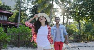 女孩举行人手夫妇走的谈的愉快微笑在热带棕榈树公园通信 股票录像