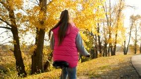 女孩举行弯曲的自行车把手的手 女孩骑马自行车和微笑在秋天公园 特写镜头 股票录像