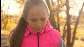 女孩举行弯曲的自行车把手的手 女孩骑马自行车和微笑在秋天公园 特写镜头 影视素材