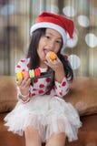 女孩举行曲奇饼板材与圣诞老人帽子的 免版税库存图片