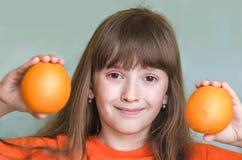 女孩举行橙色桔子和微笑 免版税库存图片