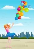 女孩举行气球 免版税图库摄影