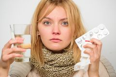 女孩举行玻璃水片剂和温度计鼻下落 得到快速的救济 方式感觉更好的快速的头疼和 图库摄影