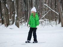 女孩乐趣滑雪通过冬天森林 免版税图库摄影