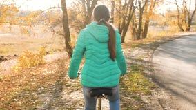 女孩乘在途中的自行车旅行 在自行车的运动的青少年的乘驾 一件高尔夫球外套的一少女在路骑自行车 股票录像