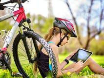 女孩乘坐在个人计算机片剂的自行车佩带的耳机循环的手表 免版税库存图片