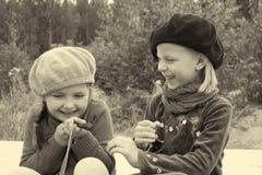 女孩互相告诉秘密,坐在公共汽车站 库存图片