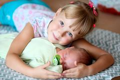 女孩五岁,与她新出生的兄弟一起花费时间,在家在卧室 库存照片