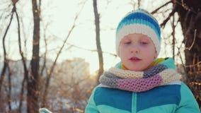 女孩五年做一张滑稽的面孔,看照相机,笑 冬天喜悦和乐趣 股票录像