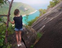 女孩享受海岛的美丽如画的看法在高度 免版税库存照片
