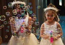 女孩享用他们的泡影枪在婚礼 免版税库存照片